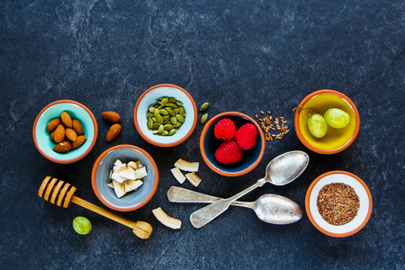 Healthy breakfast pinch bowls making with superfood ingredients: linseeds, green grapes, nuts, fresh raspberries, coconut chips and pumpkin seeds on dark vintage background, top view, flat lay