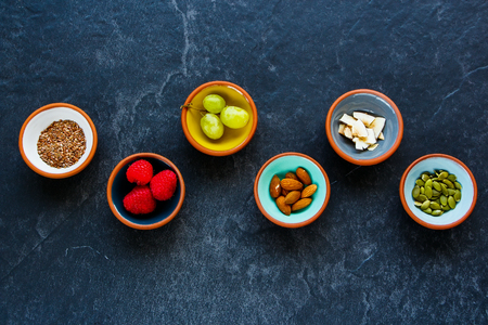 linseed: Pinch bowls of Healthy breakfast   ingredients with superfood: linseeds, green grapes, nuts, fresh raspberries, coconut chips and pumpkin seeds on dark vintage background, top view