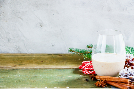 Glass of Traditional tasty winter eggnog with milk, rum and cinnamon, christmas decorations on wooden table. Concrete background, selective focus