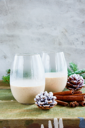Glasses of Traditional winter eggnog with milk, rum and cinnamon, christmas decorations on wooden table. Concrete background, selective focus
