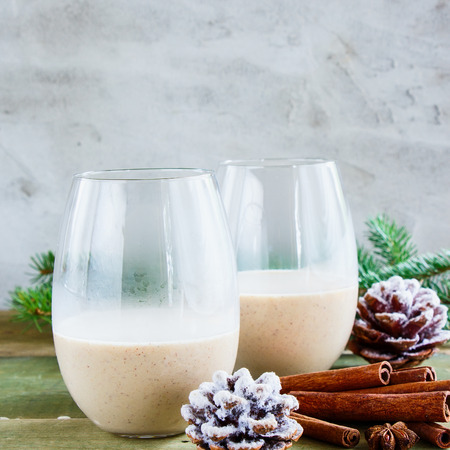 Glasses of Traditional homemade eggnog with milk, rum and cinnamon, christmas decorations on wooden table. Concrete background, selective focus, square crop