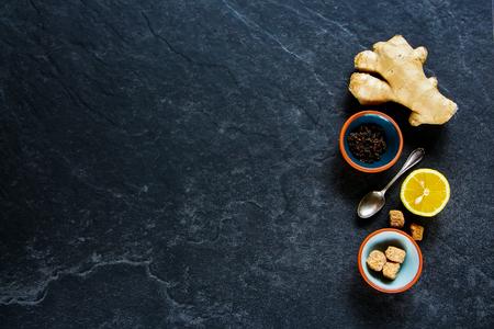 Flat-lay de composición de té negro sobre fondo de hormigón oscuro: té, limón, azúcar morena, jengibre. Espacio de copia de vista superior plana Foto de archivo - 90418416