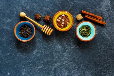 Tea concept. Flat-lay of delicious tea composition on dark concrete background: assortment of tea, honey, cinnamon sticks, anise star and brown sugar. Flat lay top view copy space