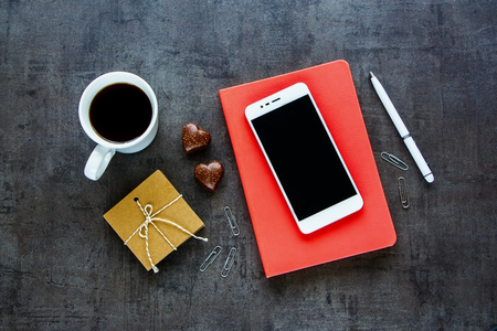 Feminine office workplace with coffee cup, chocolate, office supply, smart phone, pink notebook top view. Flat lay style. Business concept. Beautiful morning breakfast. Fashion female blogger working desk.