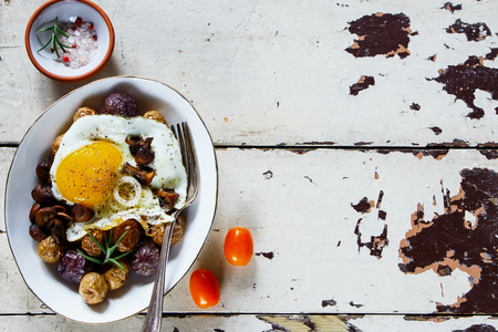 Delicious dinner of fried egg, baby potatoes and mushrooms in bowl- healthy breakfast or snack. On a white wooden table, top view, copy space