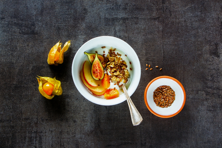Flat-lay of breakfast bowl. Homemade yoghurt with granola, fig and cape gooseberry fruit. Top view with copy space. Clean eating, vegetarian, vegan, alkiline diet food concept Stockfoto