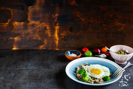 Quinoa, broccoli and egg breakfast bowl. Healthy breakfast or snack. Wooden wall background. Clean eating, diet food concept