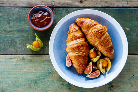 Top view of breakfast table with croissants, apricot jam and fresh ripe fruit on old wooden background, copy space.