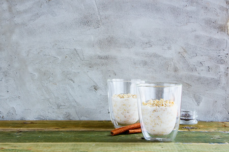 Healthy homemade overnight oats, bircher muesli with cinnamon and honey in glasses on old wooden table. Concrete wall background. Clean eating, detox, dieting, vegetarian food concept