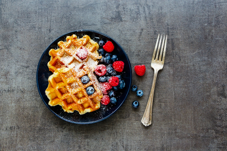 Flat lay of black plate with delicious homemade Belgian soft waffles with fresh raspberry and blueberry on dark vintage concrete textured background. Flat-lay, top view 版權商用圖片