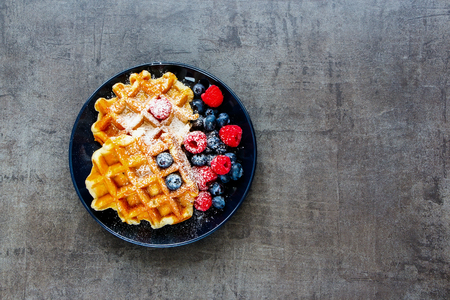 Delicious homemade Belgian soft waffles with fresh raspberry and blueberry on black plate over dark vintage concrete textured background. Flat lay, top view