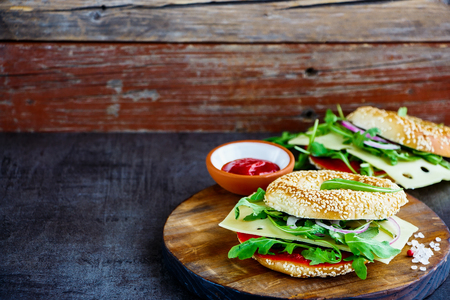 Fresh cheeseburger made of a tasty seeded bagel, cheese, tomato sauce, arugula and onion, presented on a wooden board, selective focus. Healthy breakfast food. Clean eating, diet food concept