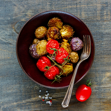 Bowl of vegan dinner flat-lay. Baked potato, brussel sprouts and cherry tomatoes on wooden background, top view, square crop. Clean eating, healthy, dieting food concept. Stock Photo