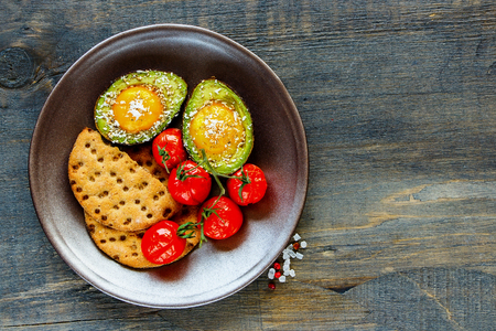 Tasty breakfast plate of cracker, tomatoes and avocado baked with eggs over dark wooden background, top view. Flat lay. Clean eating food concept. Healthy breakfast concept