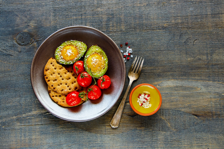 Cracker, tomatoes and avocado baked with eggs on plate over dark wooden background, top view, copy space. Flat lay. Clean eating food concept. Healthy breakfast concept