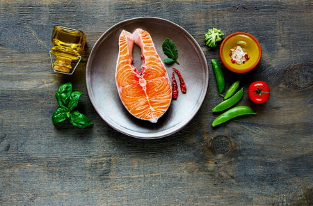 Flat-lay of raw salmon fish steak on plate and fresh vegetables on dark wooden background. Top view with space. Clean eating, dieting, power boosting, dieting concept