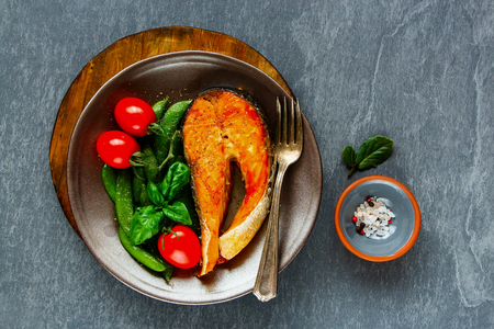 Flat lay of healthy dinner table. Grilled salmon steak on plate with green peas and tomatoes over grey stone background, top view. Diet, healthy, clean eating concept Stock Photo