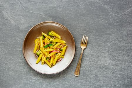 灰色のコンクリートの背景、トップビュー、コピースペースの上にプレート上の野菜とパルメザンチーズとイタリアのペンネパスタ。フラットレイ