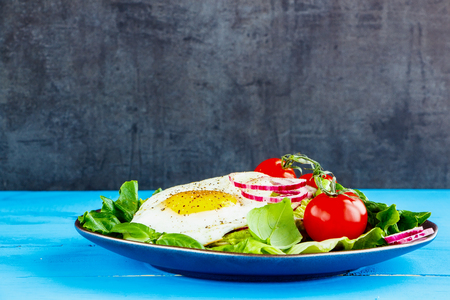 Fried egg and fresh vegetables on plate over blue wooden table, side view, selective focus. Clean eating, healthy, diet, detox food concept Stock Photo