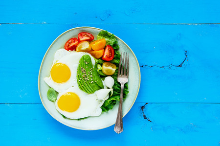 Healthy vegetarian breakfast plate flat-lay. Fried eggs, avocado and fresh vegetables on blue wooden table, top view, copy space. Clean eating and energy boosting food concept Stock Photo