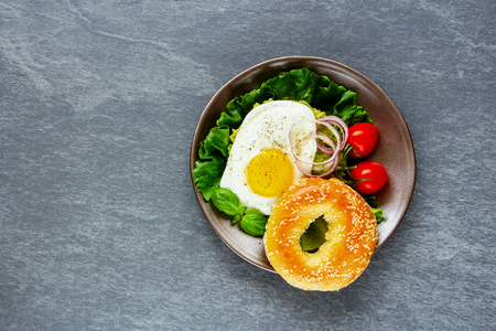 Healthy vegetarian breakfast plate - bagel with fried egg and fresh vegetables on grey concrete background, top view, copy space. Flat lay. Clean eating, healthy, diet, detox food concept
