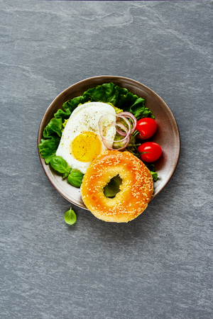Delicious vegetarian breakfast plate. Bagel with fried egg and fresh vegetables on grey concrete background, top view, vertical. Flat lay. Clean eating, healthy, diet, detox food concept Stock Photo