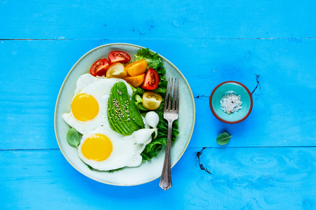 Tasty vegetarian breakfast plate flat-lay. Fried eggs, avocado and fresh vegetables on blue wooden table, top view, copy space. Clean eating and energy boosting food concept
