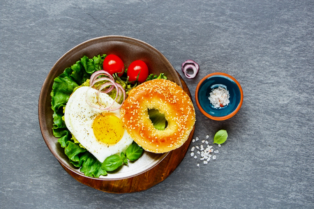 Flat lay of vegetarian breakfast plate - bagel with fried egg and fresh vegetables over grey concrete background, top view, copy space. Clean eating, healthy, diet, detox food concept Stock Photo