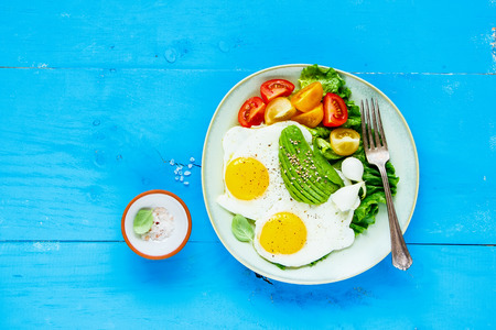 Plate of healthy vegetarian breakfast. Fried eggs, avocado and fresh vegetables on blue wooden table, top view, copy space. Flat-lay. Clean eating and energy boosting food concept
