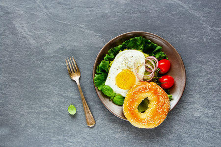 Healthy vegetarian breakfast plate flat lay. Bagel with fried egg and fresh vegetables on grey concrete background, top view, copy space. Clean eating, healthy, diet, detox food concept