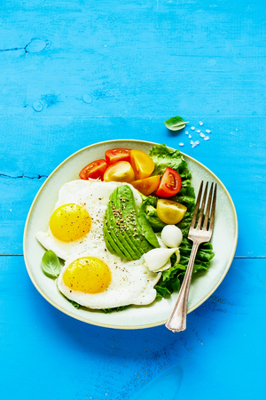 Vegetarian breakfast plate close-up. Fried eggs, avocado and fresh vegetables on blue wooden table, side view, copy space. Clean eating and energy boosting food concept