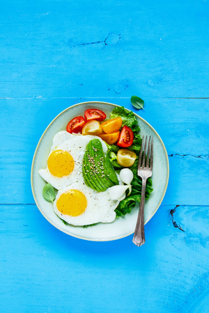 Flat-lay of vegetarian breakfast plate. Fried eggs, avocado and fresh vegetables on blue wooden table, top view, vertical. Clean eating and energy boosting food concept Stock Photo