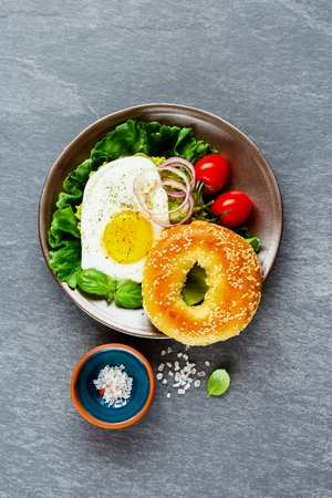 Vegetarian breakfast plate flat lay. Bagel with fried egg and fresh vegetables on grey concrete background, top view, vertical. Clean eating, healthy, diet, detox food concept Stock Photo
