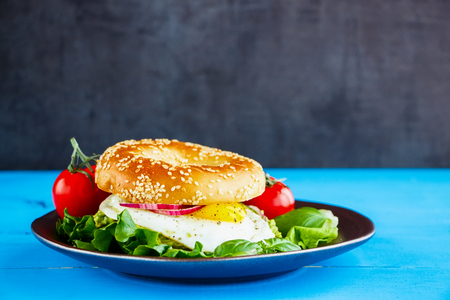 Delicious bagel with fried egg and fresh vegetables on plate over blue wooden table, side view, selective focus. Clean eating, healthy, diet, detox food concept