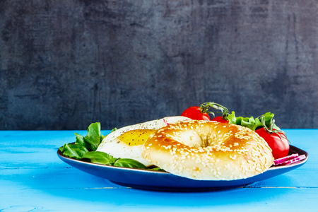 Bagel with fried egg and fresh vegetables on plate over blue wooden table, side view, selective focus. Clean eating, healthy, diet, detox food concept