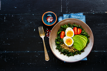 Fresh vegetarian salad bowl of quinoa, kale, tomatoes, avocado and egg over black wooden background, top view, copy space. Flat lay style. Energy boosting food concept Imagens