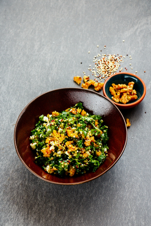 Delicious raw kale salad bowl with quinoa, feta cheese and walnut over grey concrete background. Side view. Selective focus. Clean eating, dieting, vegetarian food concept Stock Photo