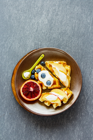 Warm traditional belgian waffles with fresh fruit and whipped cream on plate over concrete textured background. 版權商用圖片