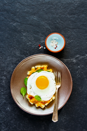 Healthy breakfast savory warm waffles with fried egg on plate over dark concrete textured copy space background. Top view. Flat lay, vertical
