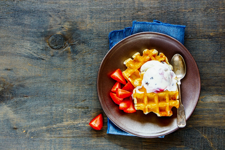 Flat lay of Homemade Belgian soft waffles with ice cream and fresh strawberry on plate over wooden copy space background. Top view.