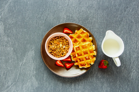 Breakfast table with belgian waffles, homemade granola, fresh strawberries and jug of milk on grey concrete textured copy space background. Top view. Flat lay. Health food concept.
