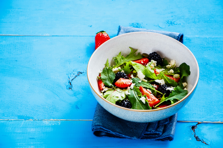 Close up of fresh strawberry salad bowl with arugula, feta cheese and blackberry on blue painted wood background. Side view, selective focus