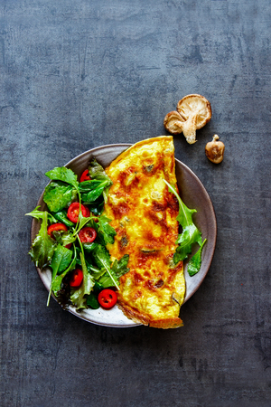 Fresh mushroom omelette with salad on plate over dark concrete copy space background. Healthy food concept. Flat lay, top view, vertical
