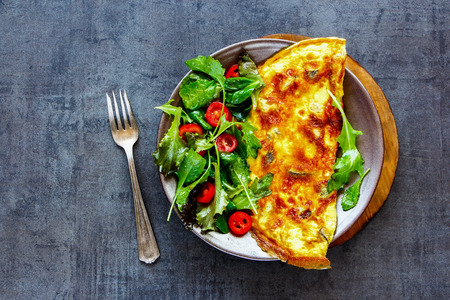 Plate of homemade mushroom omelette with fresh salad on dark concrete copy space background. Healthy food concept. Flat lay, top view