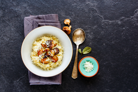 Flat-lay of delicious porcini mushrooms risotto bowl with parmesan cheese on dark stone copy space background. Healthy food concept. Top view Foto de archivo - 98387475