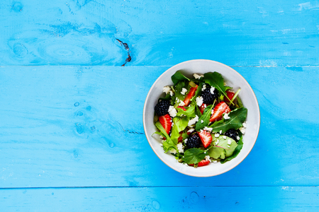 Fresh strawberry salad bowl with arugula, feta cheese and blackberry on blue painted wood background. Flat lay, top view