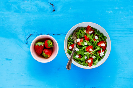 Bowl of strawberry arugula feta cheese salad served on blue painted wood copy space background. Flat lay, top view