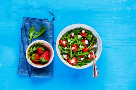 Freshly made arugula strawberry feta cheese salad bowl served on blue painted wood copy space background. Flat lay, top view 写真素材