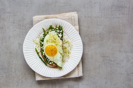 Green aspargus, fried egg, feta cheese and micro greens spring sandwich on plate over light concrete background. Healthy eating, slimming, diet lifestyle concept. Flat lay, top view