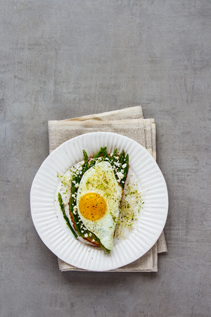 Plate of green aspargus, fried egg, feta cheese and micro greens spring sandwich over light concrete background. Healthy eating, slimming, diet lifestyle concept. Flat lay, top view Фото со стока